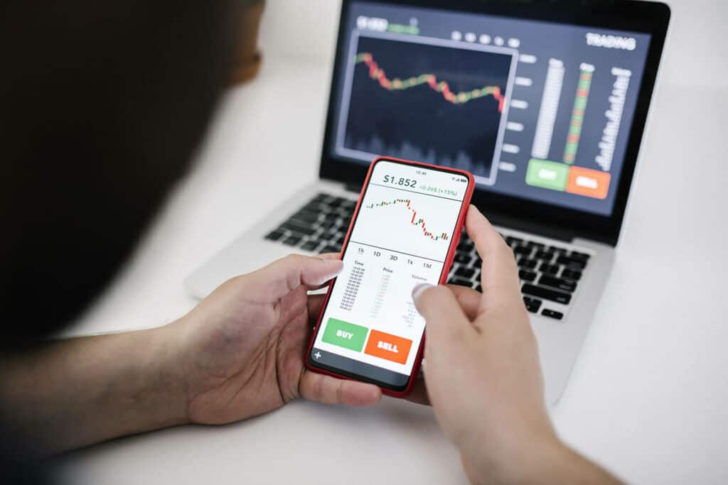 Person using mobile to trade crypto with laptop on table