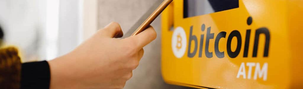 Person holding mobile phone in front of yellow bitcoin atm